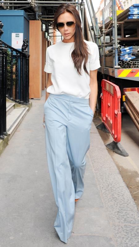 Victoria Beckham wearing blue pants and cream blouse