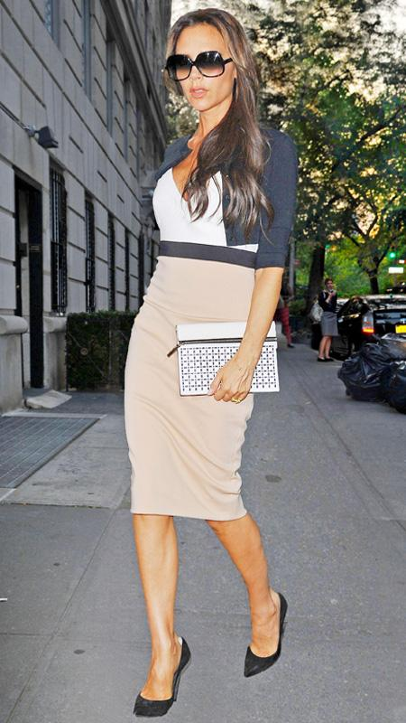 Victoria Beckham in beige and white dress with navy cardigan