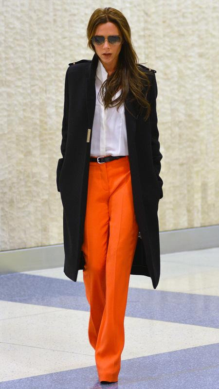 Victoria Beckham wearing orange pants, white top, and black trench coat