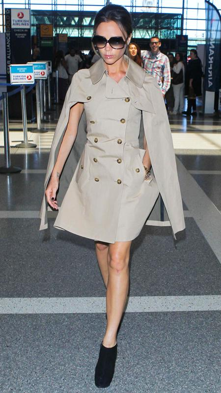 Victoria Beckham wearing tan double button trench cape coat