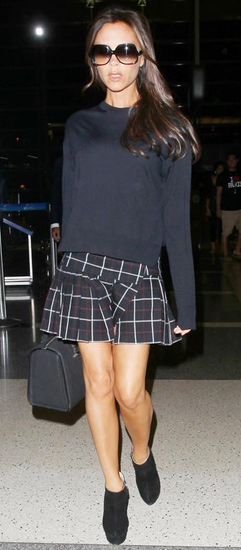 Victoria Beckham in sweater and checkered skirt